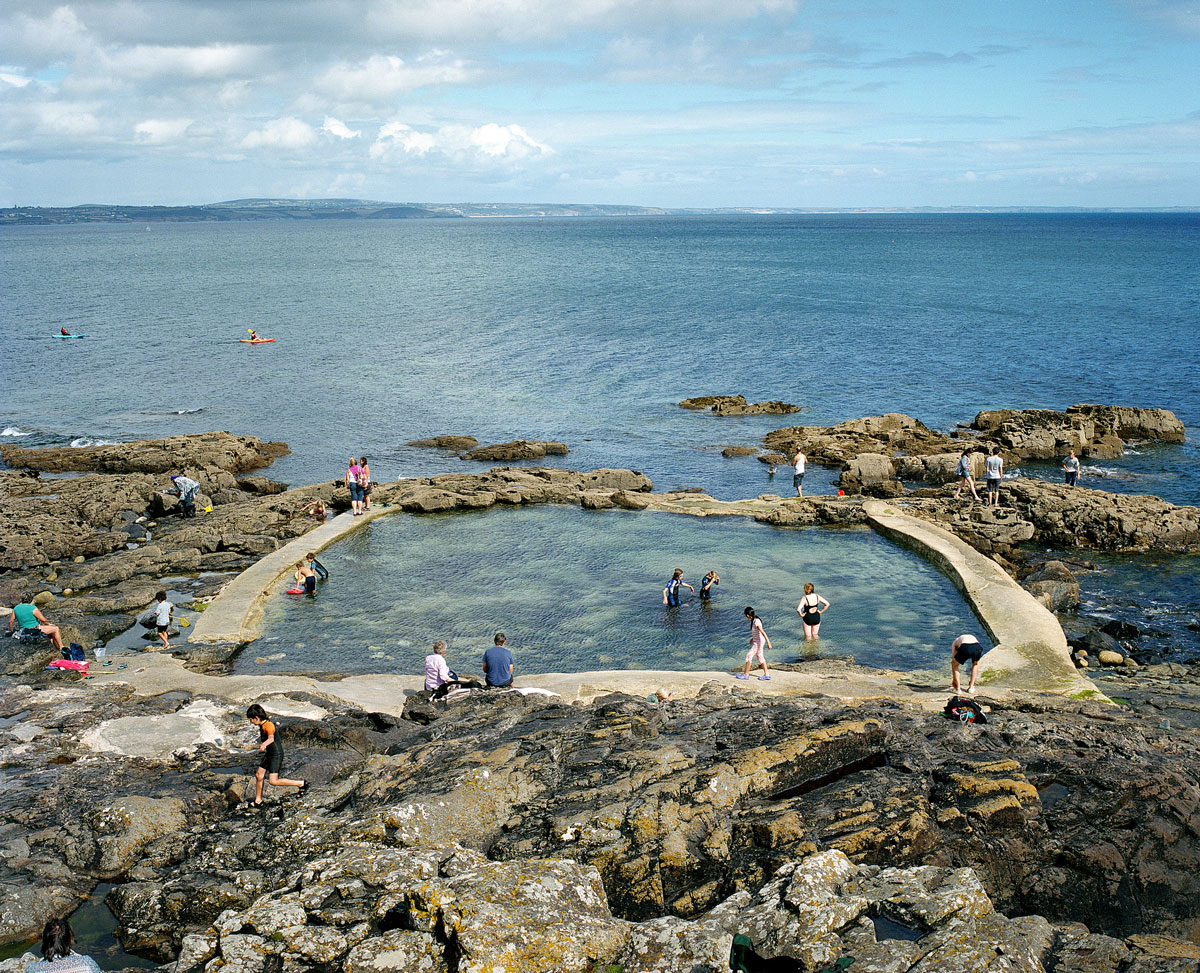 Mousehole Tidal Pool, Cornwall, UK. Until the 1950s and the rise of the heated indoor swimming pool, children learnt to swim outdoors. For those close to the sea, many man-made tidal swimming pools were constructed around Britain's coastline. Heated by the sun, these tidal pools were often built to keep bathers safe from high and rough seas, which explains why so many of them are clustered in Scotland and around the surfing beaches of Cornwall. Whether they are simple swimming holes made by shoring up natural rock pools or grand lido-like pools complete with lifeguards and tea huts, they are all refreshed by good high tides.